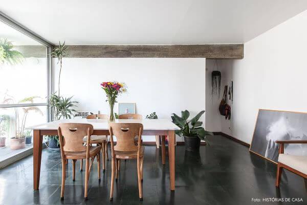 Sala de jantar com piso de ardósia preta e mesa de madeira