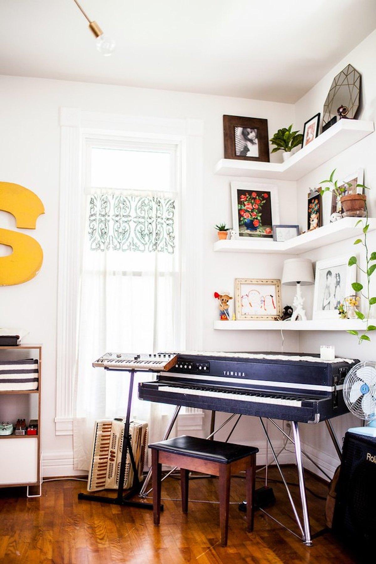 Sala de música com estante de canto de corda com quadros e enfeites lindos