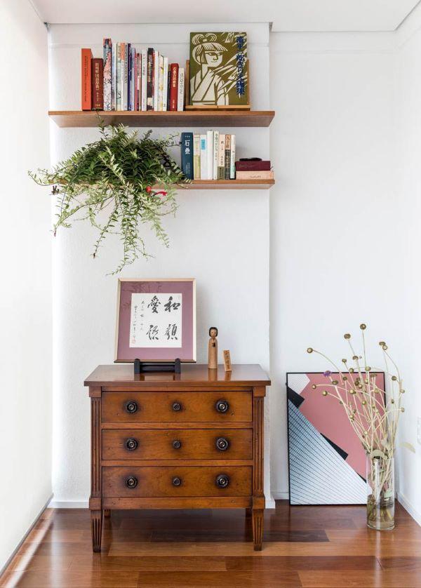 Sala decorada com móveis vintage de madeira e prateleira decorada com plantas