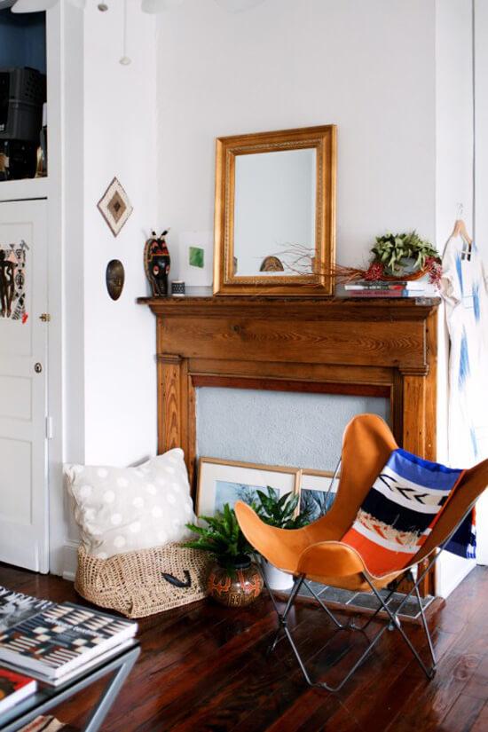Sala decorada com poltrona butterfly laranja no estilo boho