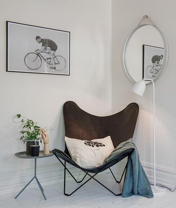 Sala decorada com poltrona butterfly marrom e manta azul
