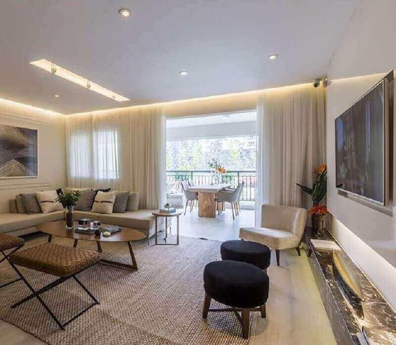 Sala grande decorada em cores neutras com puff banqueta redondo Foto Pinterest