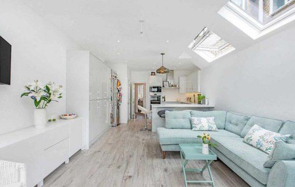 Sala minimalista e branca com sofá pé palito na cor azul claro