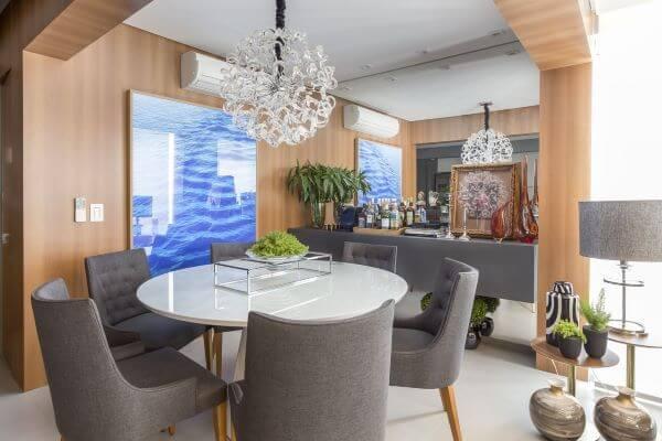 Sala pequena com mesa de jantar branca redonda e cadeiras cinza