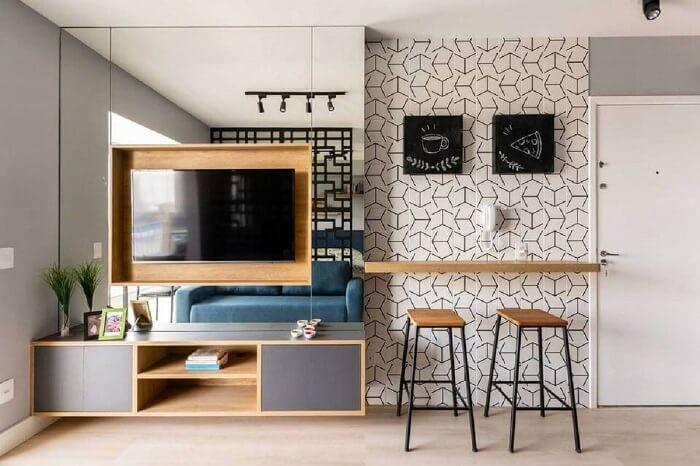 Sala planejada pequena com rack suspenso e painel de TV com acabamento espelhado. Projeto de Zark Studio Lab