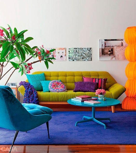 Sala retrô colorida com sofá pé palito verde e poltrona azul na mesma cor que o tapete