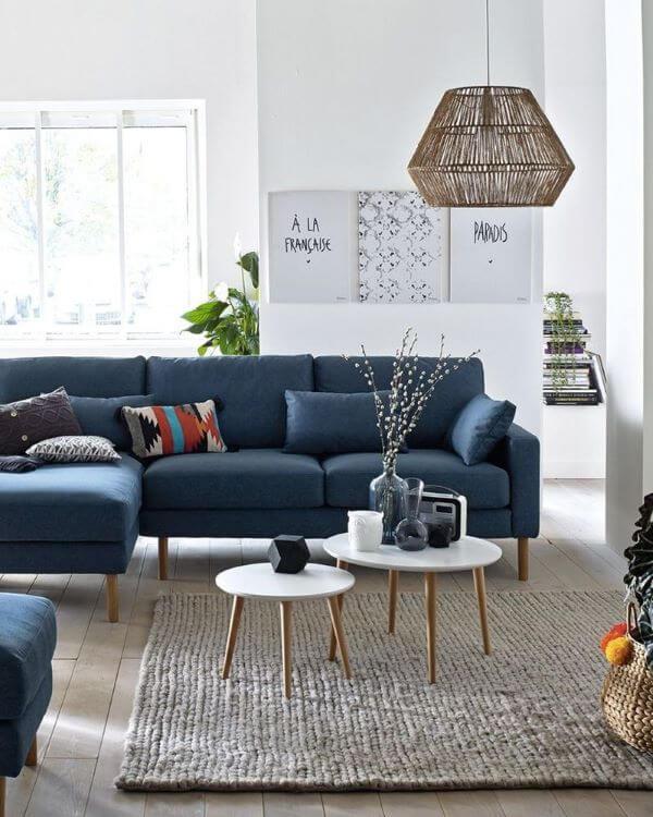 Sofá azul marinho com pé de palito e mesa de centro retrô na sala clean e sofisticada