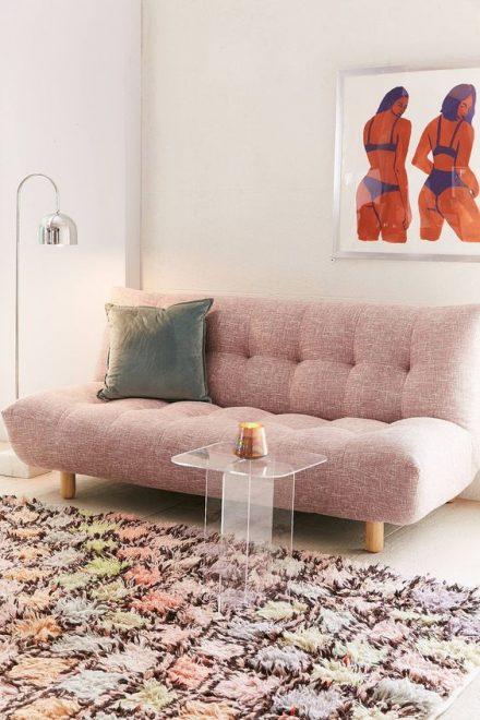 Sofá cama com pés de palito e decoração em tons pasteis