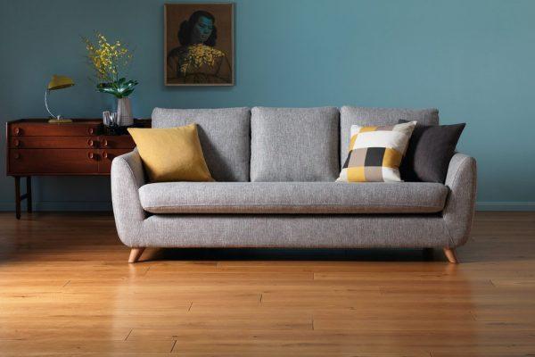 Sofá clássico com pés de palito e almofadas neutras