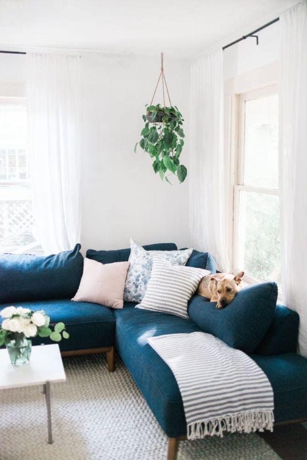 Sofá pé palito com chaise de canto azul marinho com manta e almofadas neutras