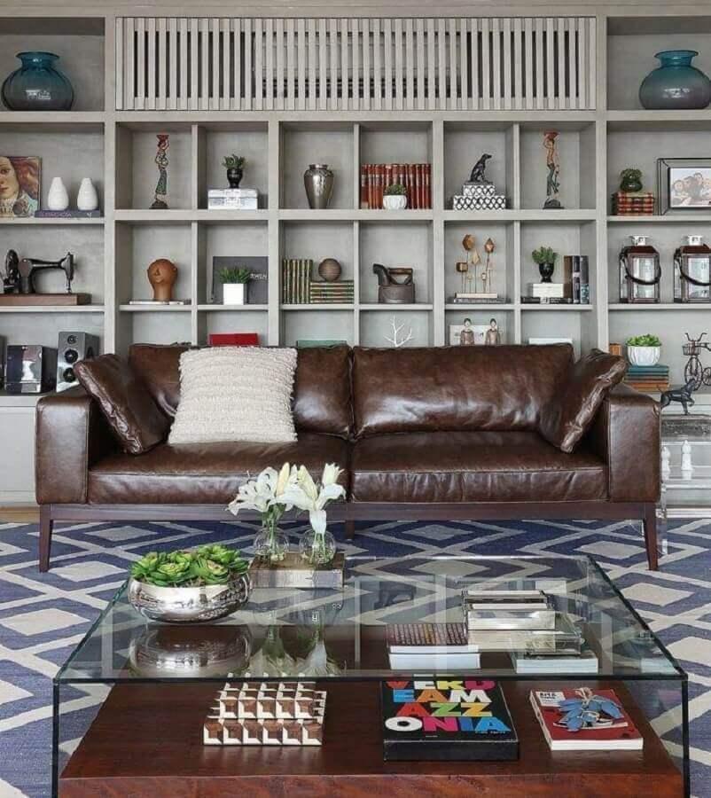 Tipos de sofas de couro para decoracao de sala com estante de nichos e mesa de centro de vidro Foto Mariana Orsi Fotografia