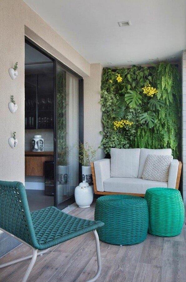 Varanda decorada com jardim vertical e puff banqueta redondo Foto Histórias de Casa