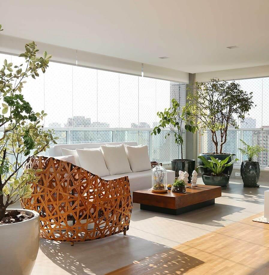 Varanda moderna com cortina de vidro e sofá com almofadas grandes