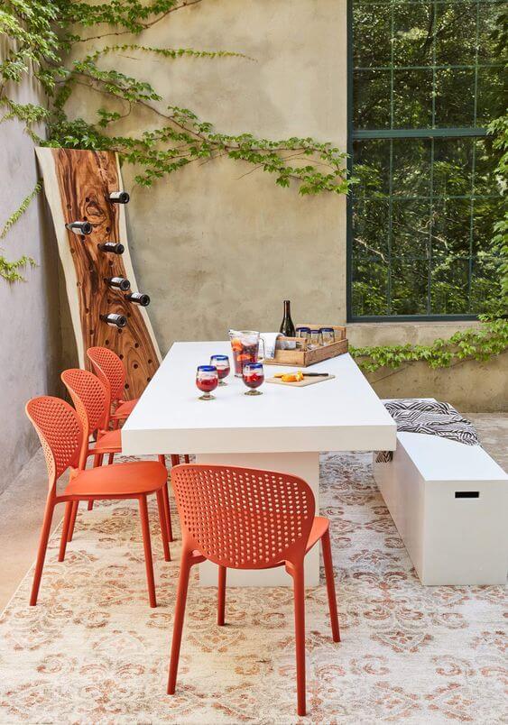 Cerâmica para área externa com mesa de jantar branca e cadeiras laranja