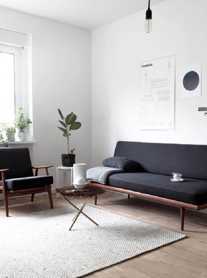 Sala decorada com sofá pé palito e poltrona preta de madeira