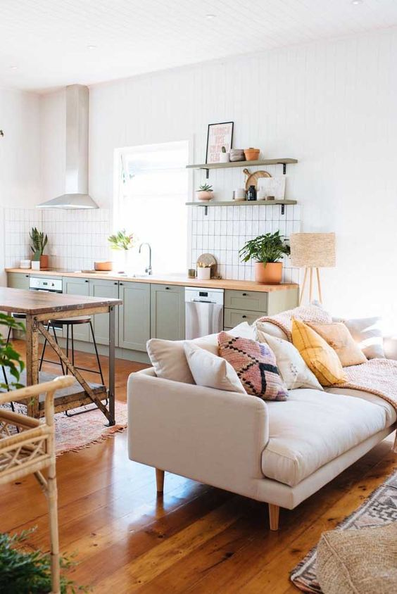 Casa no conceito aberto com sofá pé palito creme e armários de cozinha