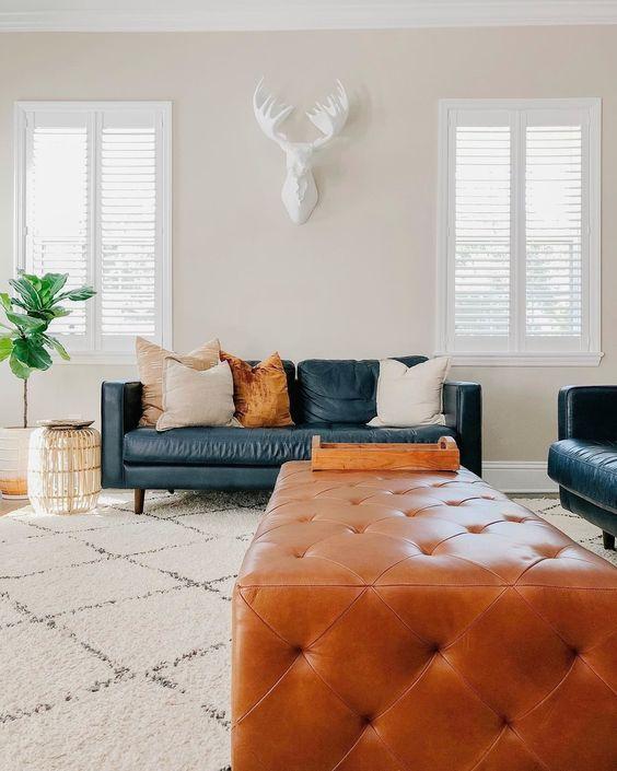 Sala com sofá de couro com pé palito e puff capitonê