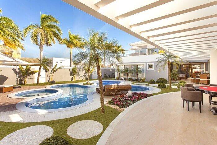 Área de lazer com piscina moderna e pergolado de concreto. Fonte: Iara Kílaris