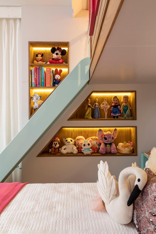 Nichos iluminados expõem brinquedos da menina. Projeto de Marta Calasans