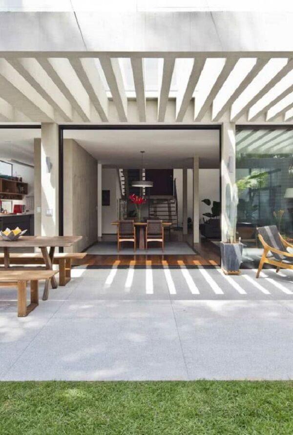 A área com pergolado de concreto com vidro pode ser usada até em dias de chuva. Fonte: Decor Fácil
