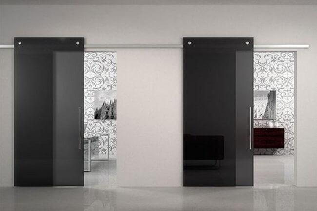 A porta de vidro fume para sala ajuda a separar ambientes de quarto e banheiro. Fonte: Elegant Doors and Glass