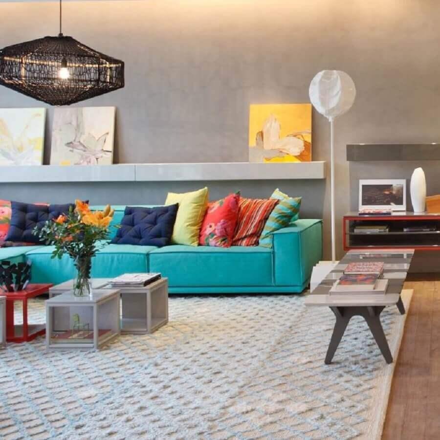 Almofadas coloridas para sofá cor ciano em sala moderna decorada com parede de cimento queimado Foto Paula Neder Arquitetura
