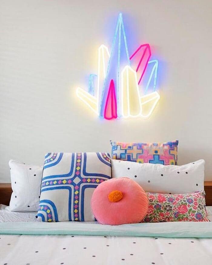 Almofadas divertidas decoram o quarto neon feminino. Fonte: Electric Confetti