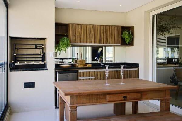 Apartamento com churrasqueira pequena na área gourmet e moveis de madeira rústicos