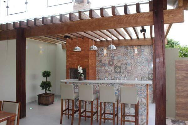 Área de churrasqueira pequena com pergolado de madeira e vidro revestimento colorido