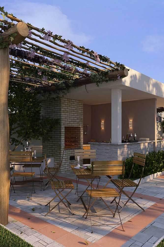 Área de churrasqueira pequena de tijolinho e pergolado decorado com plantas