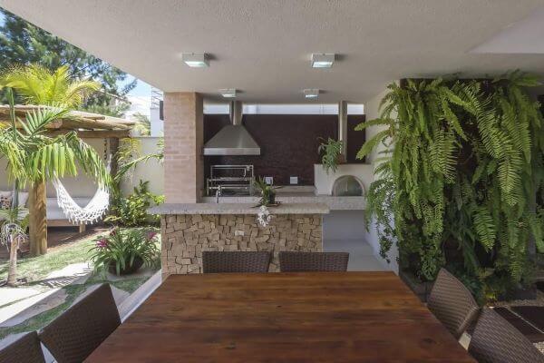 Área de lazer com churrasqueira pequena e decoração com plantas de jardim vertical