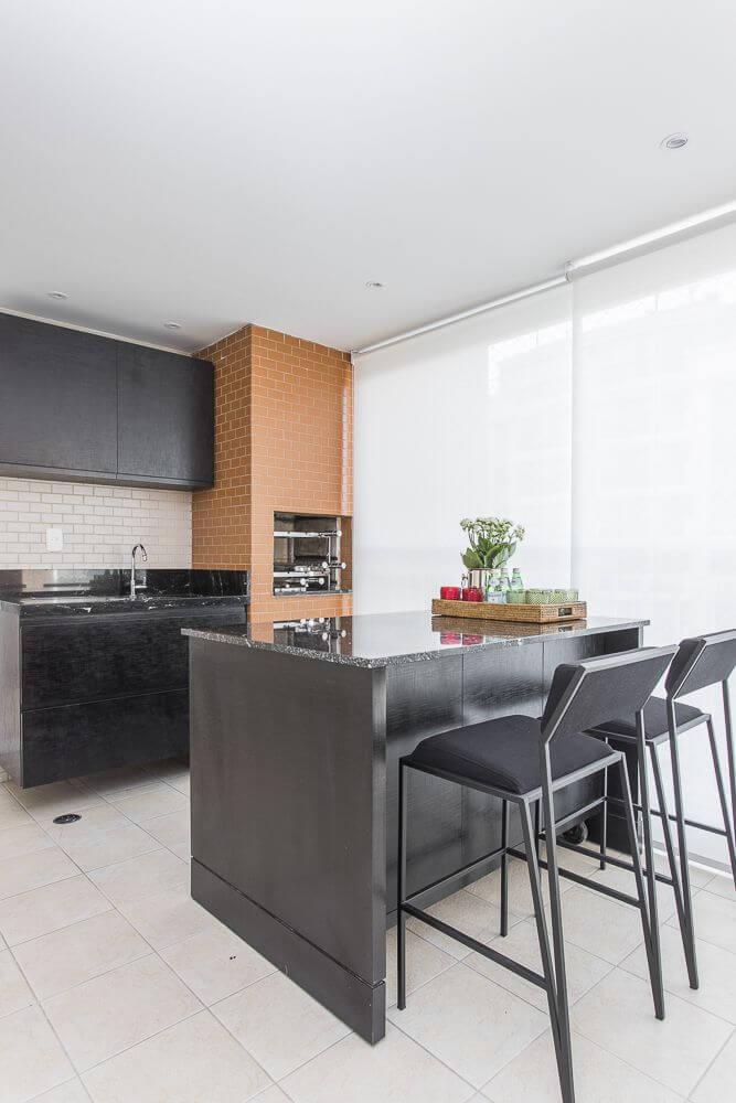 Área gourmet com churrasqueira pequena de tijolinho e bancada preta de granito