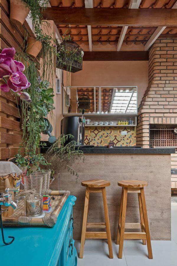 Área gourmet com churrasqueira pequena de tijolinho e jardim vertical perto da mesa azul