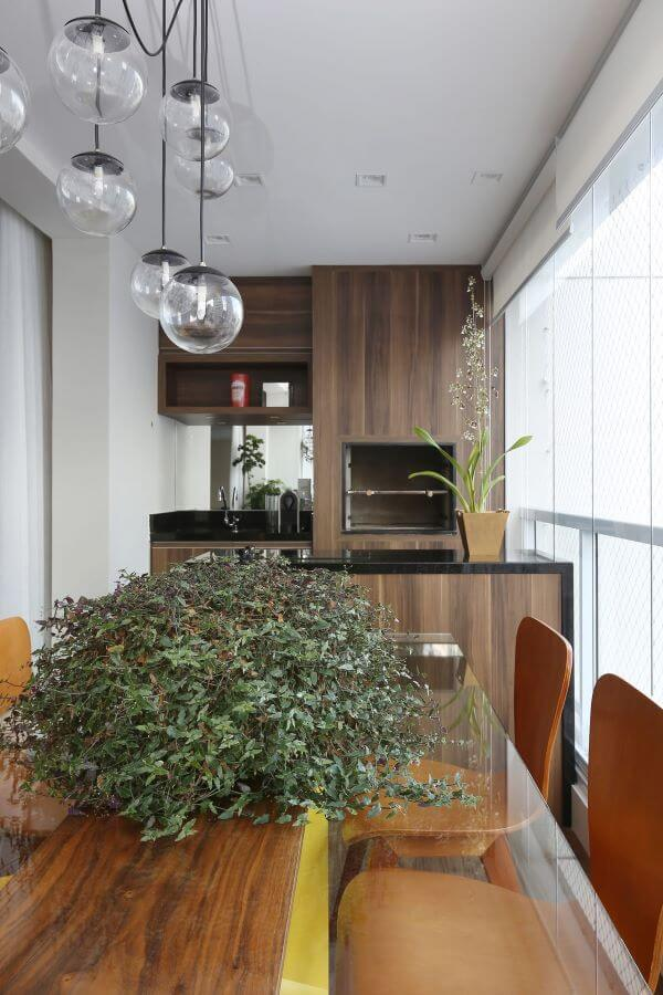 Área gourmet pequena com churrasqueira embutida e revestimento de madeira