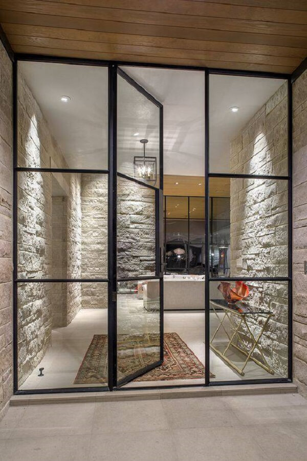 As portas de ferro com vidro para sala combinam perfeitamente com paredes de pedra. Fonte: Krausch Architectural Windows & Doors