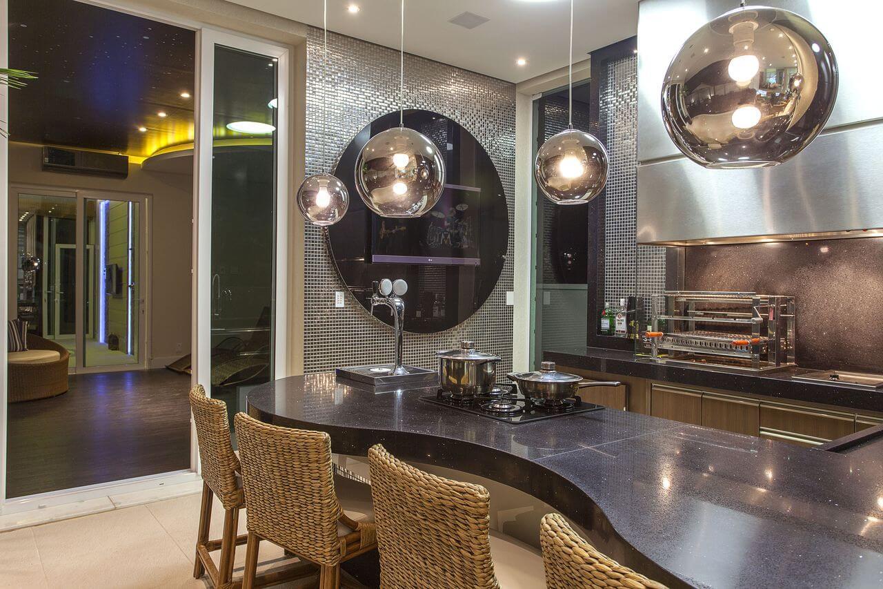Balcão de cozinha iluminado com lustre na cor prata e revestimento de pastilha na mesma cor