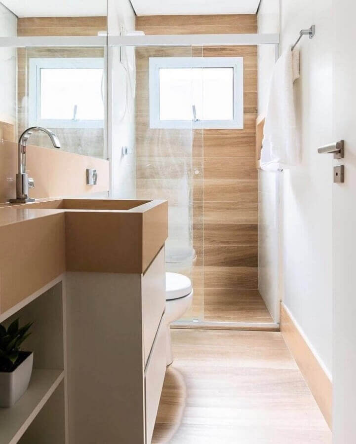 Banheiro pequeno com piso de madeira decorado com gabinete e bancada planejada Foto CW Arquitetura e Design