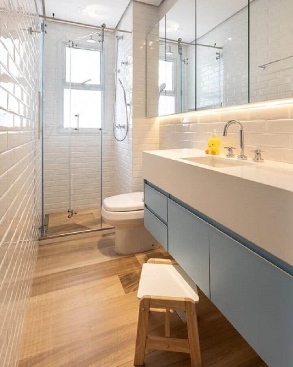 Banheiro pequeno com piso de madeira decorado com metro white e gabinete azul pastel Foto Marina Carvalho