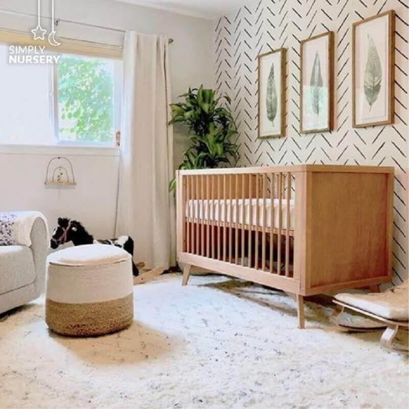 Berço cor de madeira para quarto branco decorado com vaso de planta e puff redondo Foto Simply Nursery