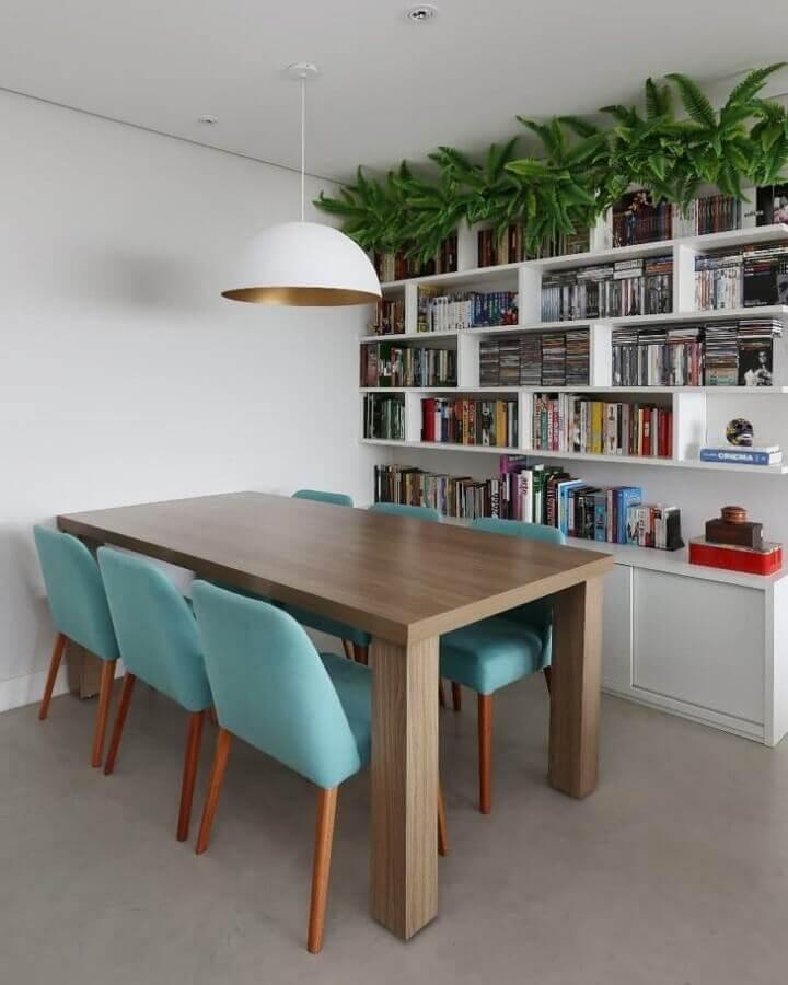 Cadeira cor azul ciano para decoração de sala de jantar com estante branca para livros Foto GF Projetos