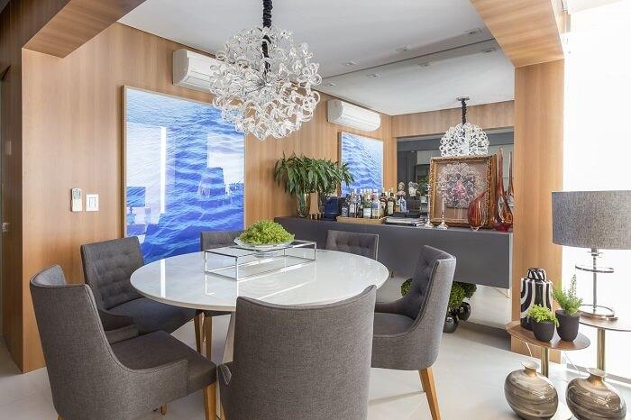Cadeiras de luxo para sala de jantar em tom cinza e lustre de cristal. Fonte: Altera Arquitetura