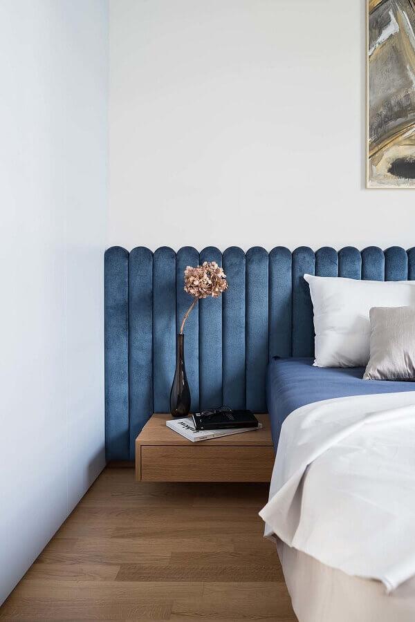 Cama com cabeceira almofadada azul planejada para decoração de quarto branco com criado mudo suspenso de madeira Foto Dwell