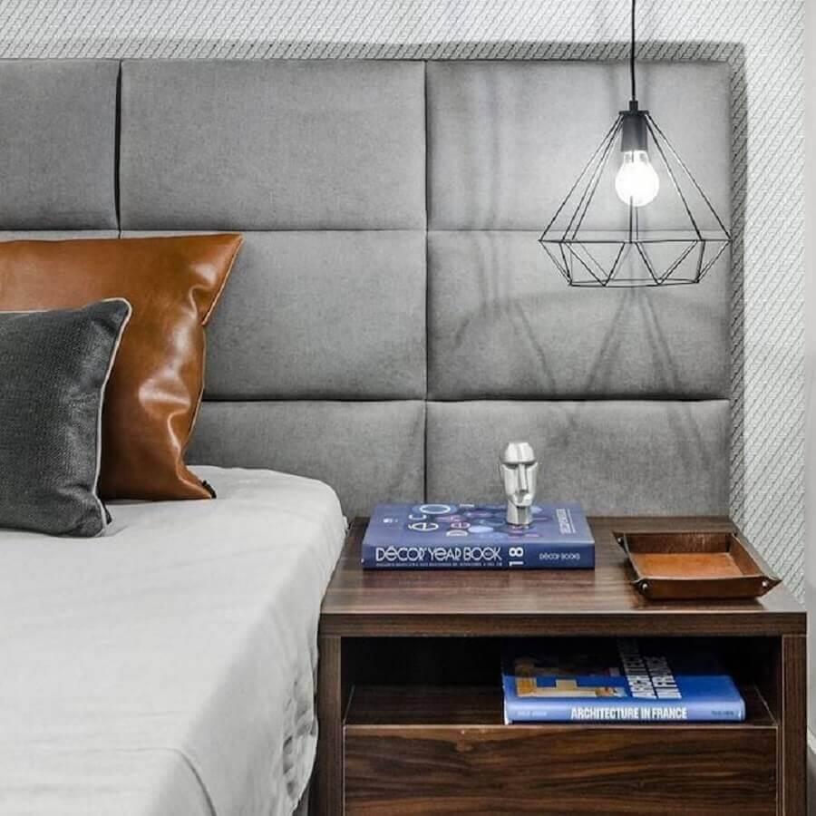 Cama com cabeceira almofadada cinza para quarto decorado com luminária pendente e criado mudo de madeira Foto Gustavo Martins