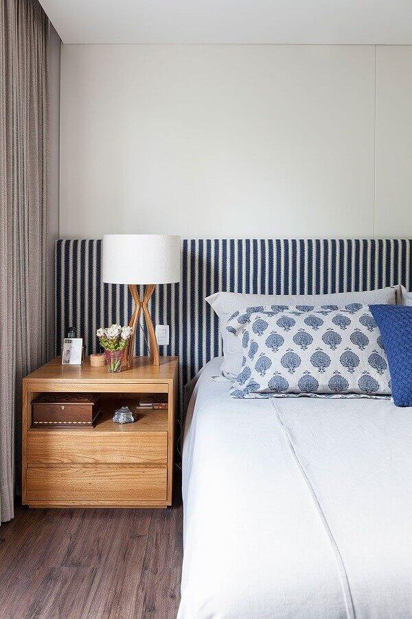 Cama com cabeceira almofadada listrada para quarto branco decorado com criado mudo de madeira Foto R A P Arquitetura