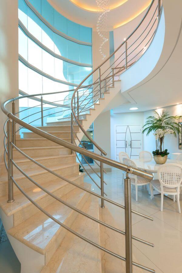 Casa com escada e mesa de jantar decorada com vaso de flor para sala