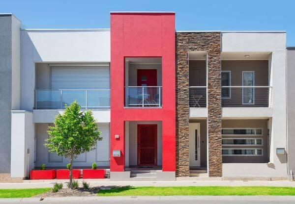 Casa com fachada de vidro e revestimento vermelho