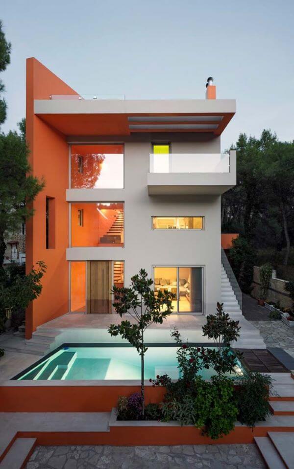 Casa laranja com fachada de vidro e piscina na entrada