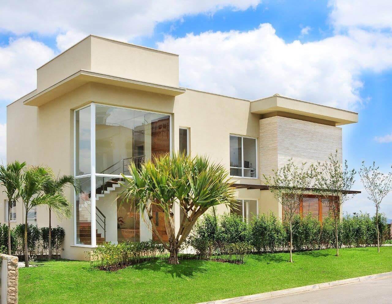 Casa moderna com fachada de vidro e jardim