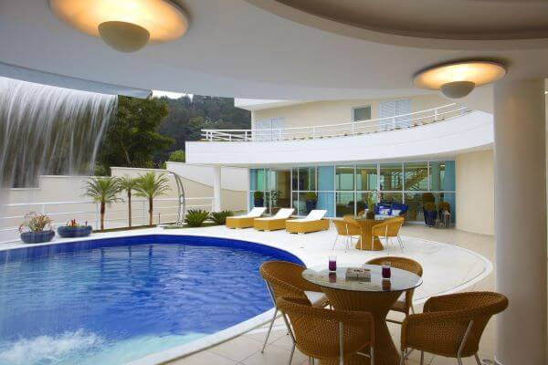 Chaise área externa com espreguiçadeiras na beira da piscina