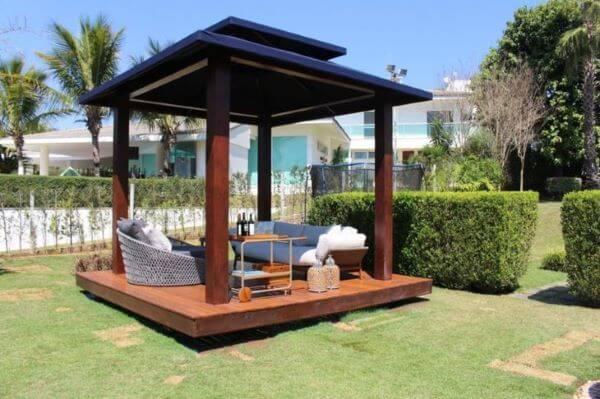 Chaise área externa no pergolado de madeira com sofá e carrinho bar